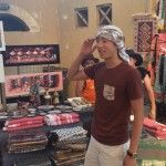 Jeffrey Sun '17 tries out the wares in a market in Jerash. Photo Credit: David Miller